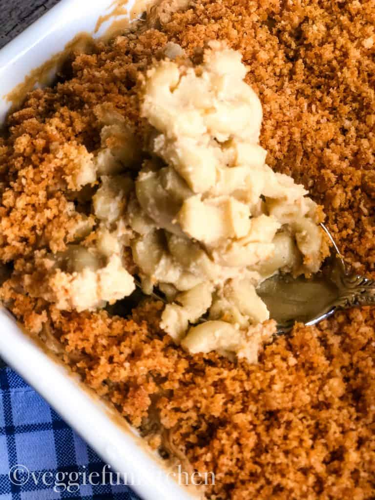 vegan baked mac and cheese in pan with spoon dipping out a portion