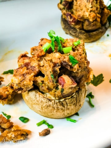 close up of two vegan stuffed mushrooms on white tray