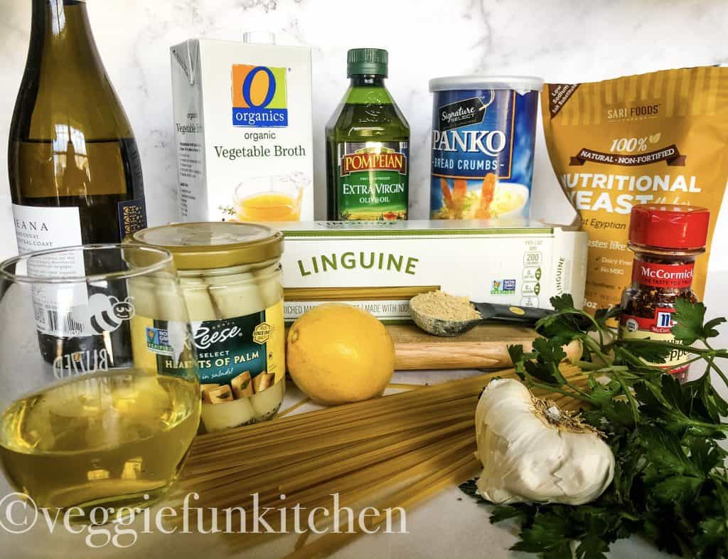 Ingredients for vegan scampi including: white wine, hearts of palm, lemon vegetable broth, olive oil, bread crumbs pasta, garlic, nutritional yeast, parsely,