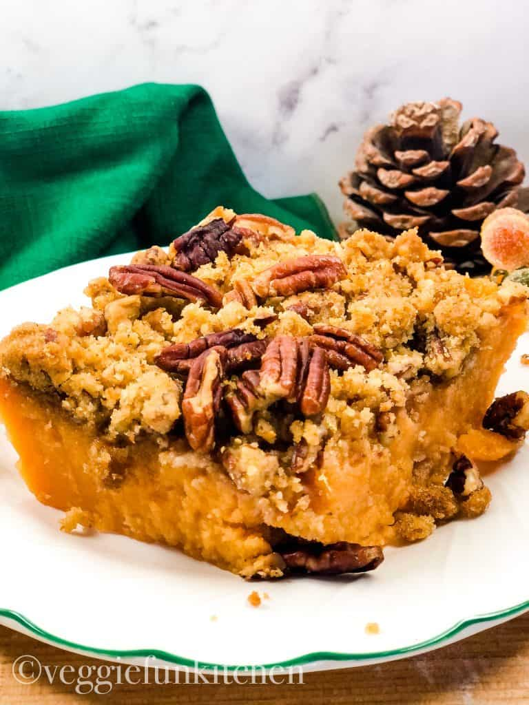 sweet potato casserole on plate with green napkin and pinecone in background