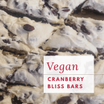 vegan cranberry bliss bars cut up on parchment with text overlay