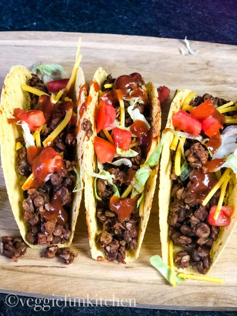 three tacos with vegan lentil taco meat on wooden board