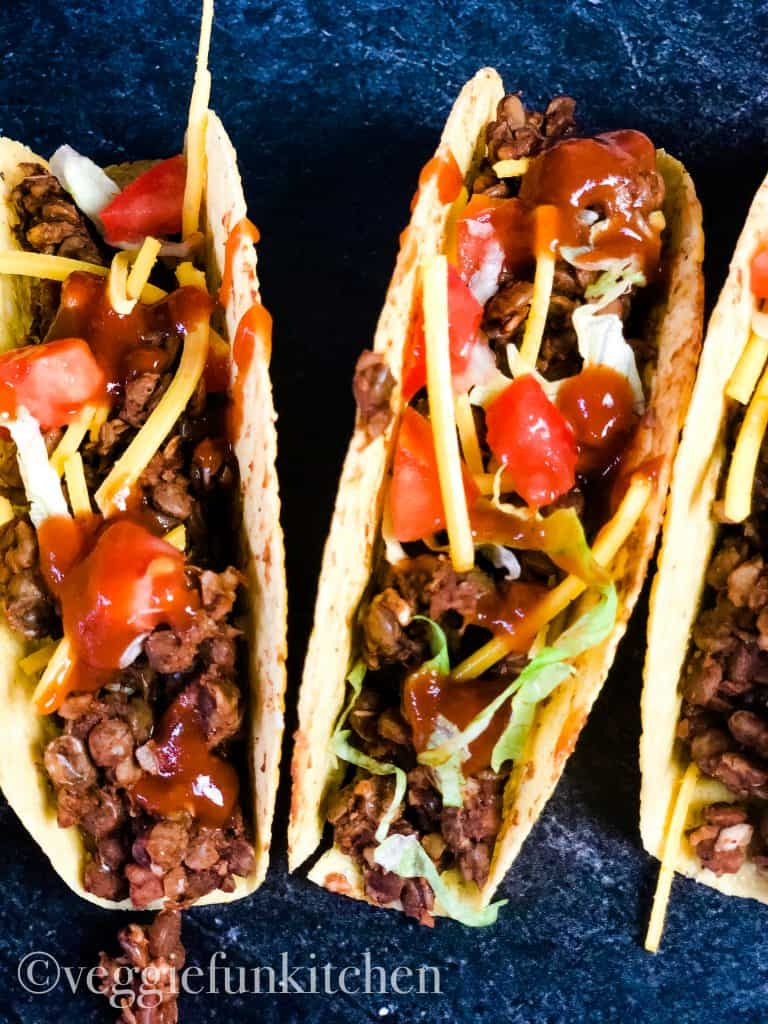 three tacos with vegan lentil taco meat on dark background