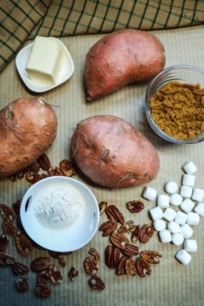 ingredients for praline sweet potatoes including three sweet potatoes, vegan butter, brown sugar, flour, pecans and dandies vegan marshmallows