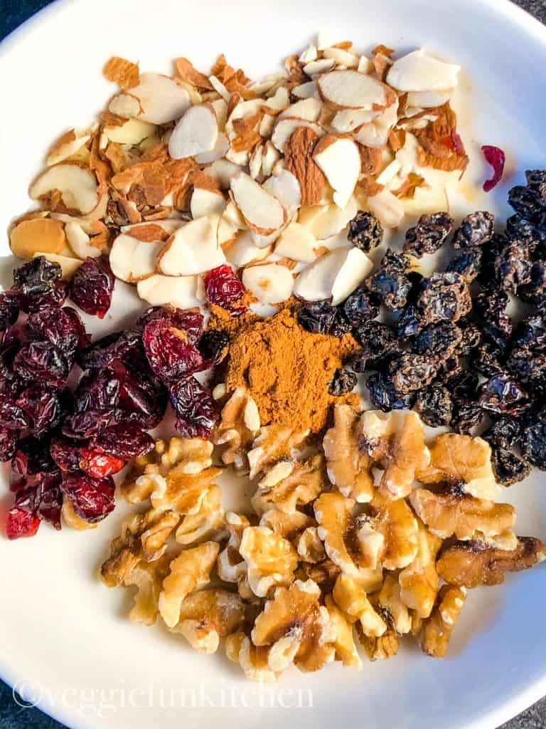 walnuts, almond slices, raisins,and cranberries in white bowl