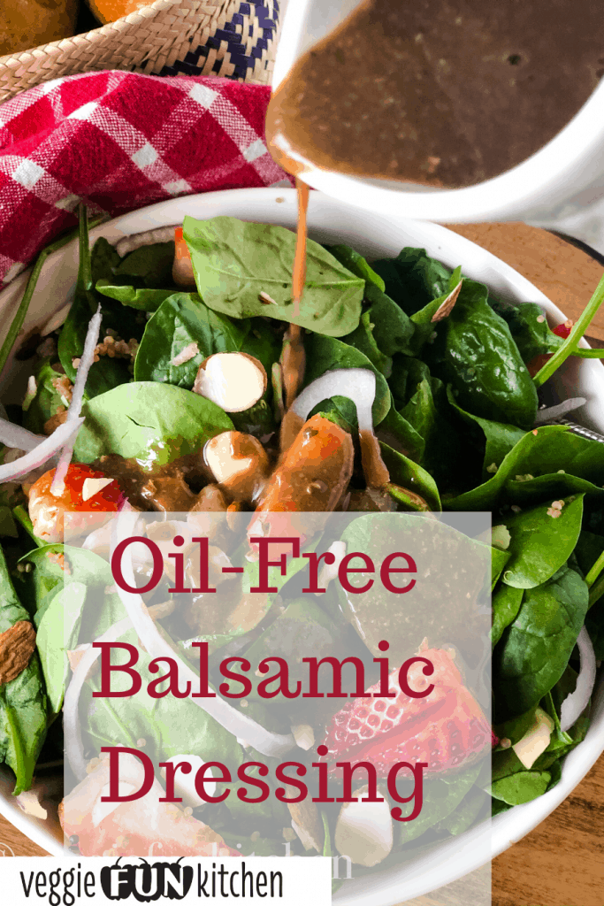 balsamic oil-free dressing pouring on spinach salad out of white container with text overlay