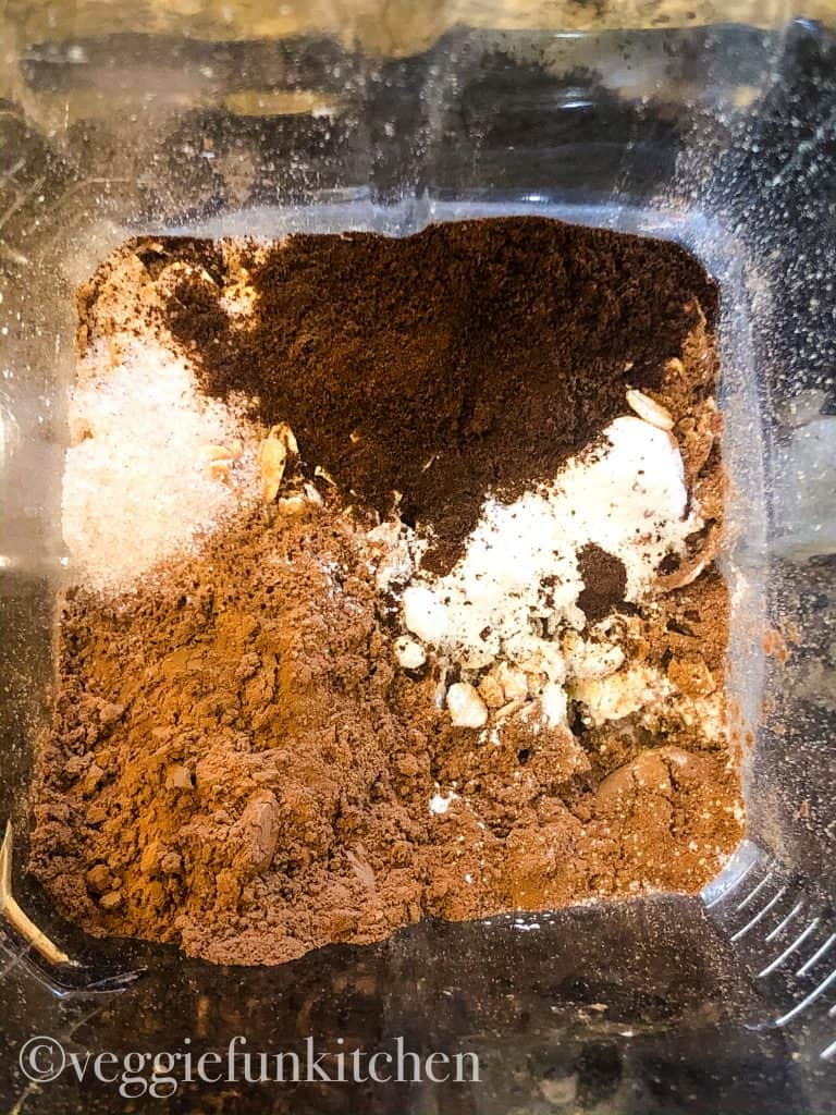 dry ingredients for black bean brownies in blender including: old fashioned oats, cocoa powder, instant coffee, salt, baking powder