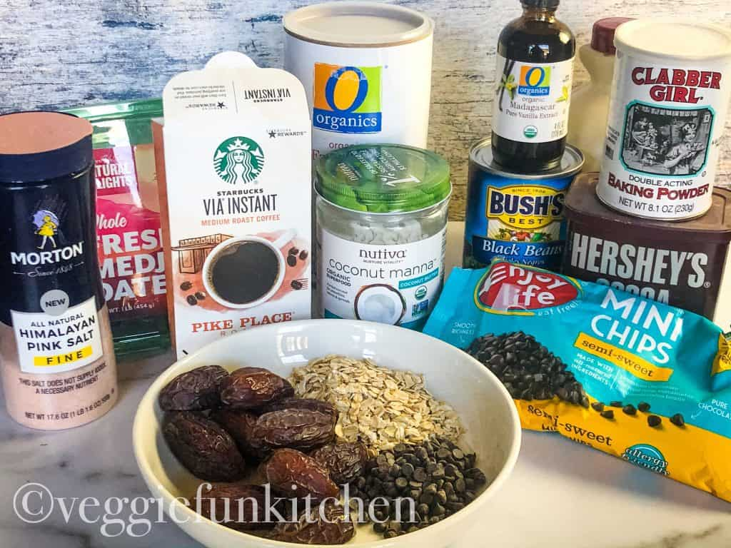 ingredients for black bean brownies including instant coffee, medjool dates, oats, coconut butter, black beans, vanilla, cocoa powder, vegan chocolate chips, baking powder, maple syrup