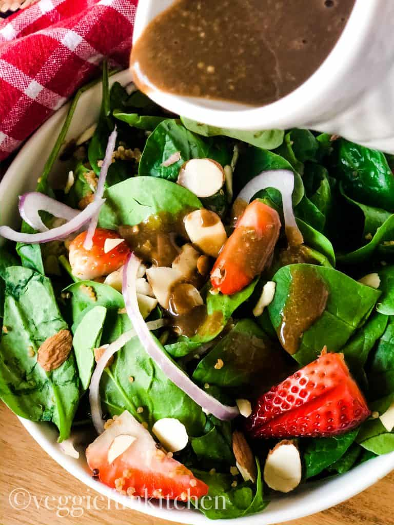 balsamic oil-free dressing pouring on spinach salad out of white container
