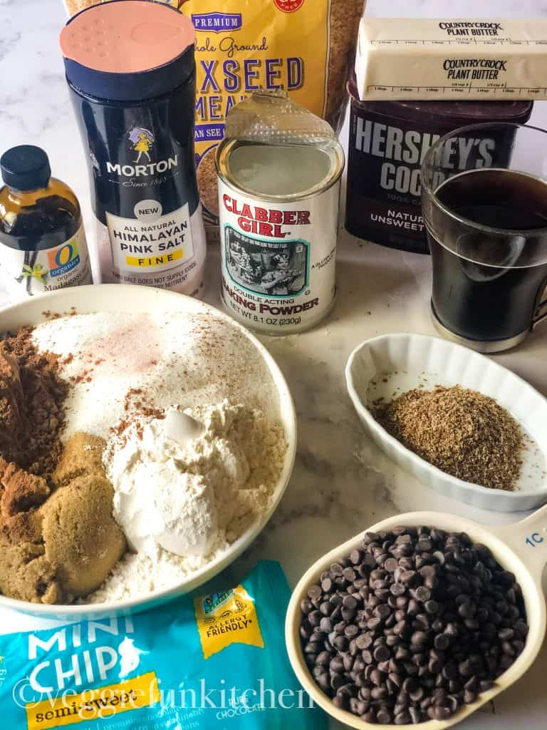 ingredients for vegan fudge brownies including cocoa powder, brown and white sugars, all purpose flour, chocolate chips, ground flax, baking powder, salt, vanilla, coffee, vegan butter