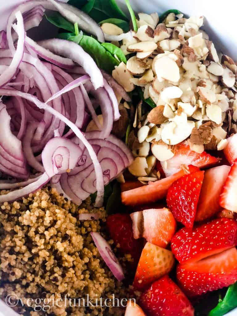 prepared ingredients for strawberry spinach salad in bowl ready to be tossed - including sliced red onions, cooked quinoa, quartered strawberries, sliced almonds, and baby spinach
