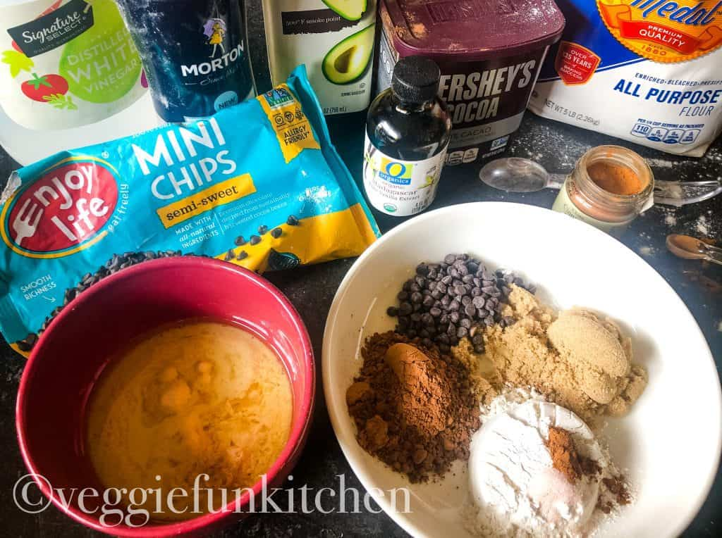 ingredients for brownie mug including flour, cocoa, brown sugar, chocolate chips, vanilla, cinnamon, salt, oil, and plant milk with vinegar