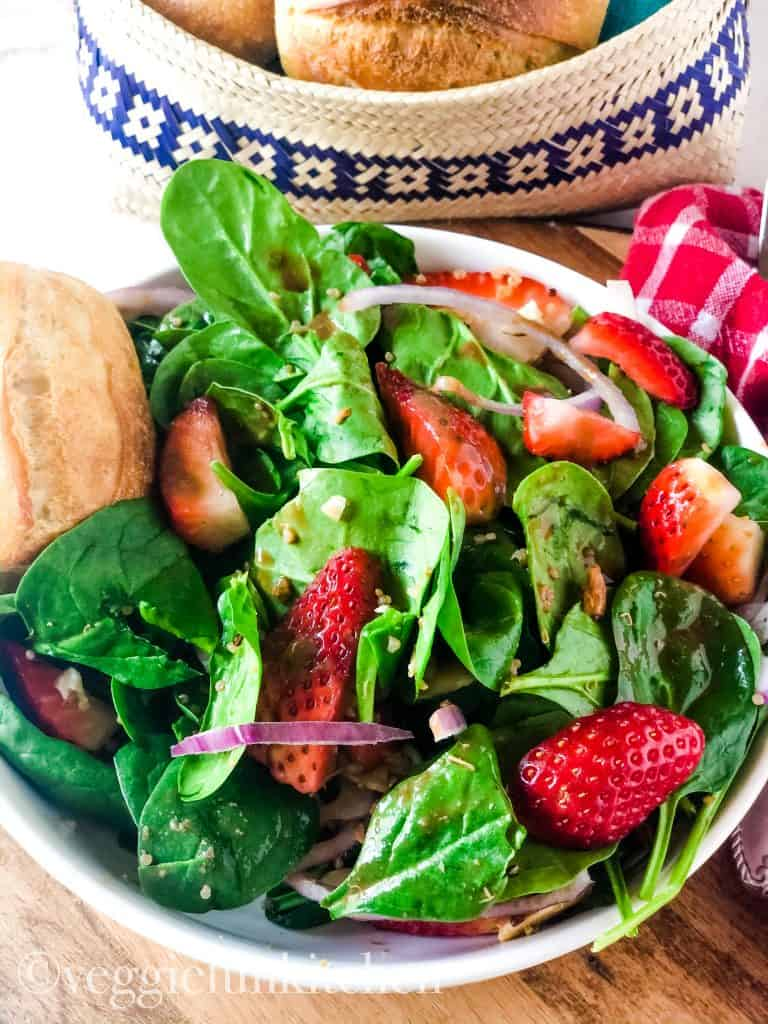 strawberry spinach salad in white bowl with red check napkin in background and dinner roll at side of bowl