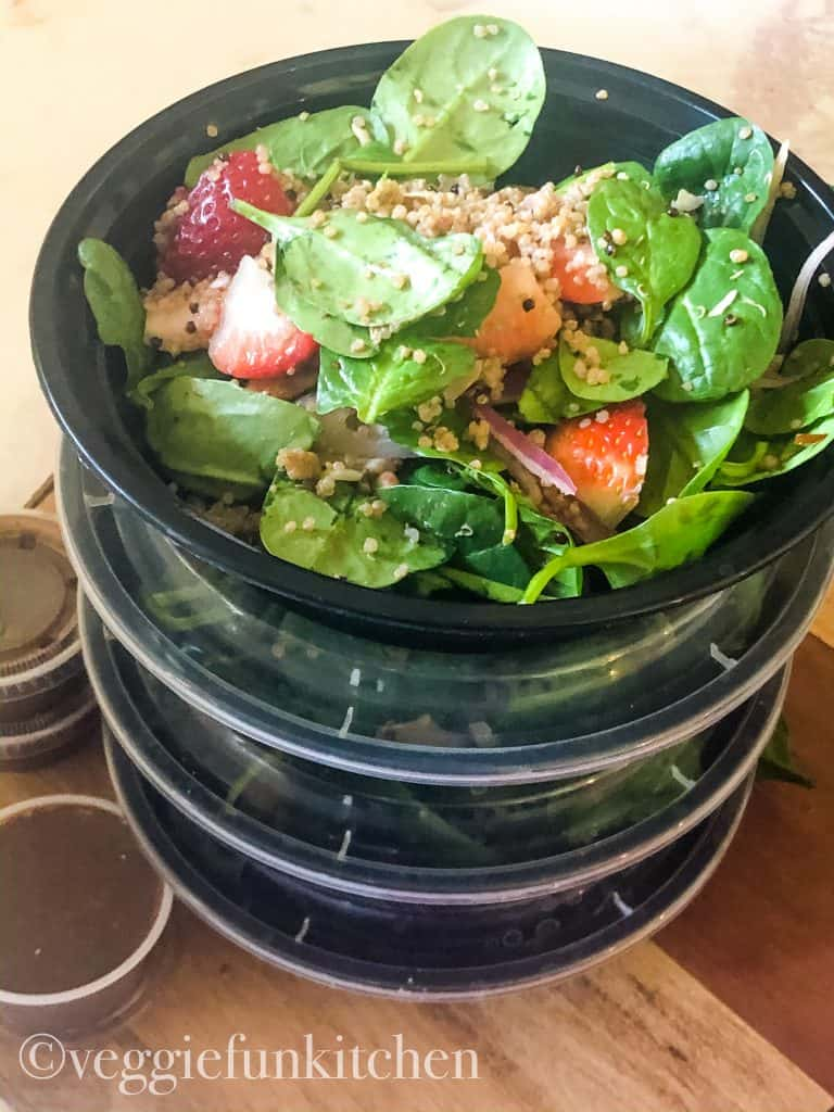Strawberry spinach salad in four round meal prep containers with dressing in containers on the side.
