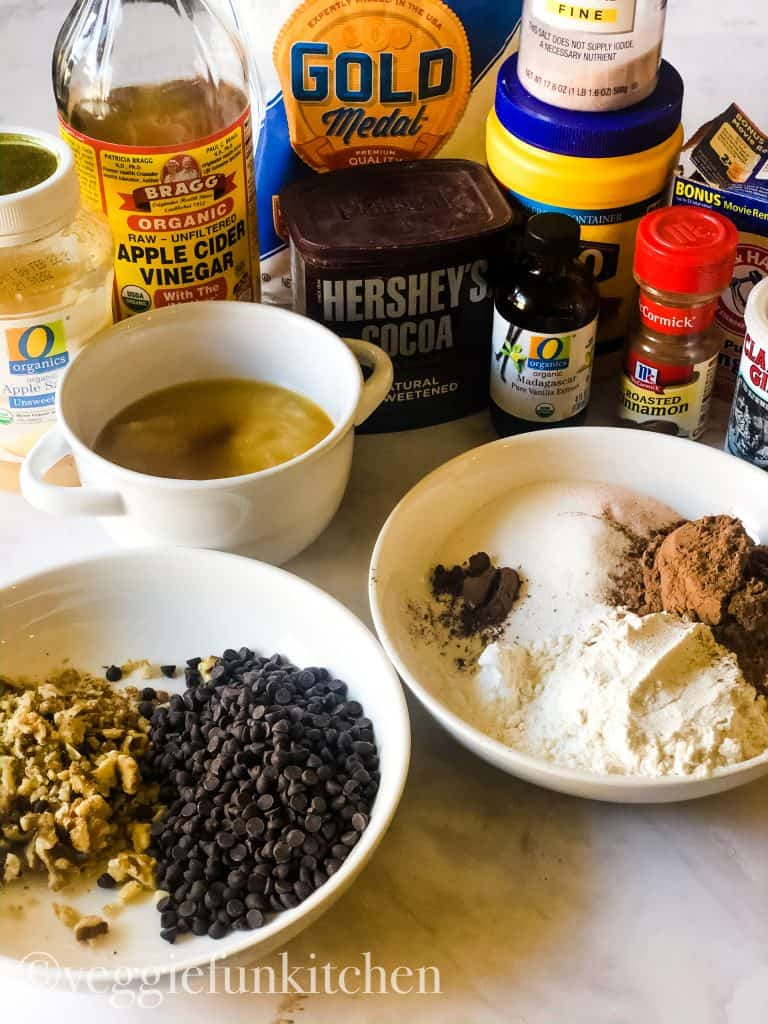 ingredients for vegan brownies including applesauce, sugar, vanilla, flour, cocoa, baking powder, chocolate chips
