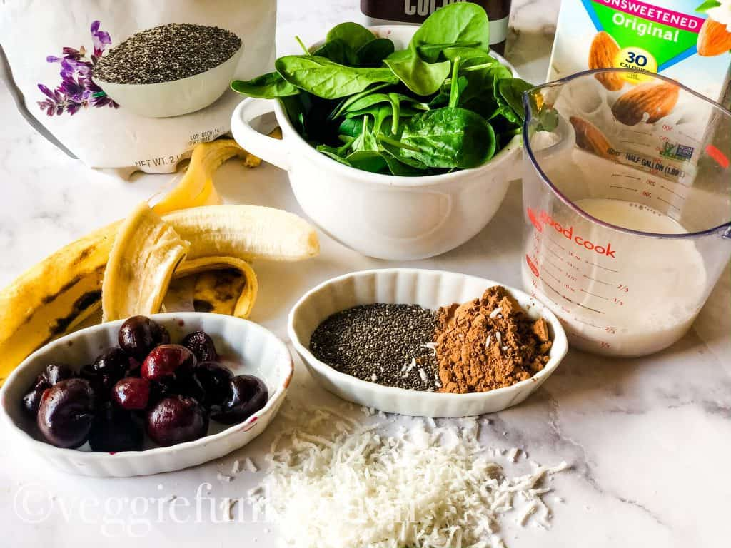 ingredients for black forest cake smoothie including cherries, banana, chia seeds, spinach, cocoa powder, almond milk