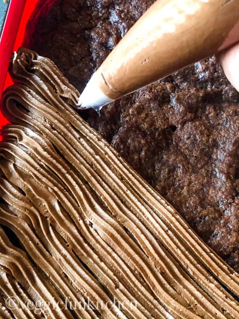 baked brownies in red pan being frosted with icing bag and star tip and at a diagonal across