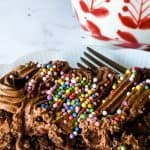 frosted brownie on white plate with white and red mug in background