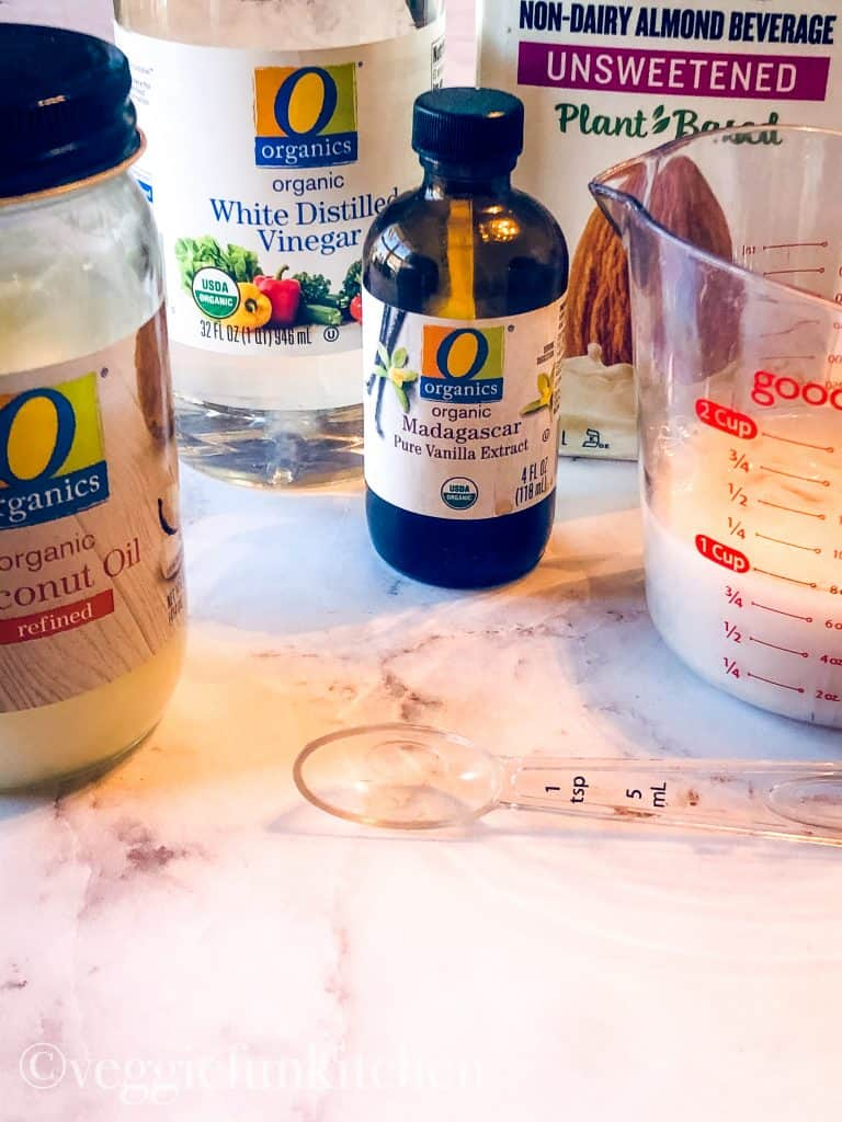 wet ingredients for brownies including coconut oil, white vinegar, vanilla extract, and almond milk