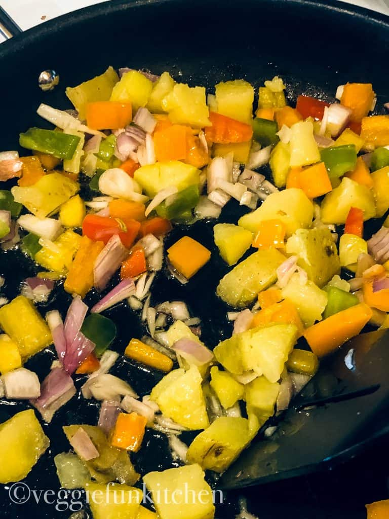 shallots, peppers, and potatoes in frying pan