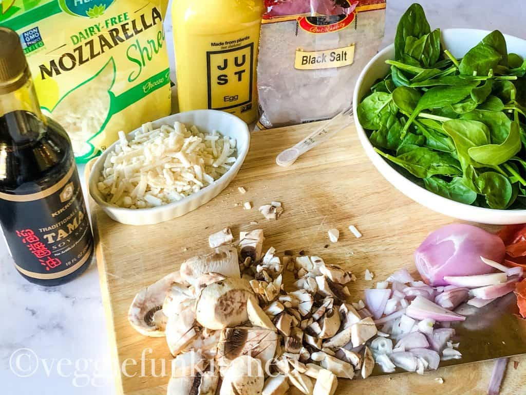 ingredients for vegan scrambled eggs included just egg, mushrooms, shallot, spinach, black salt, vegan cheese