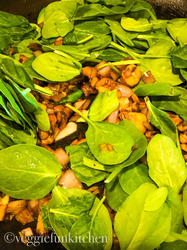 baby spinach added to shallots and mushrooms