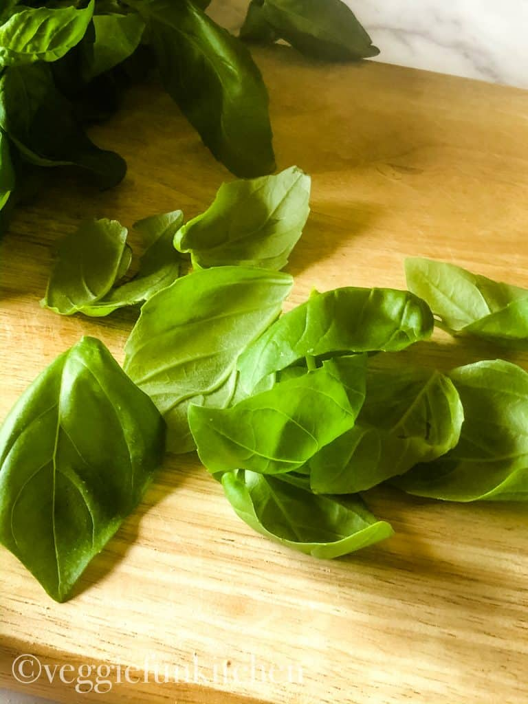 basil leaves on wooden cutting board