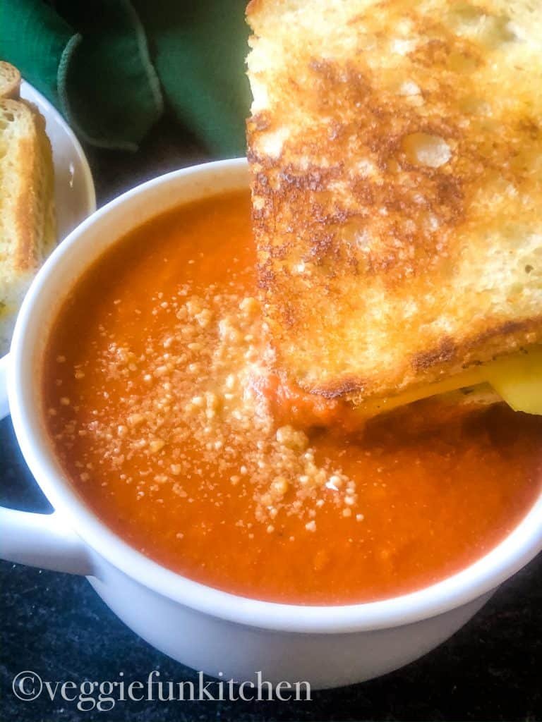 tomato soup with vegan parm on top with vegan grilled cheese dipped