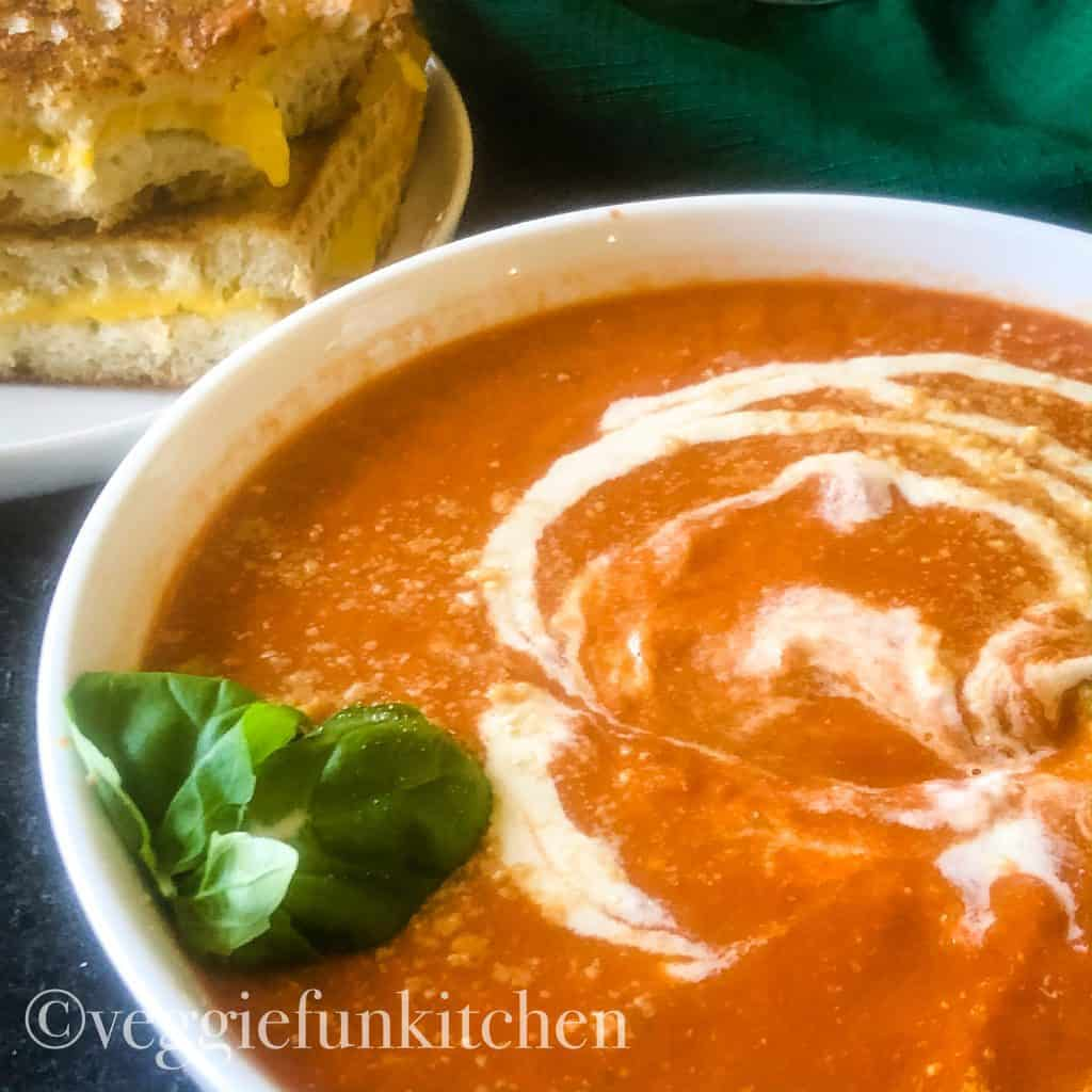 tomato soup with cashew cream drizzled on top with vegan grilled cheese in background