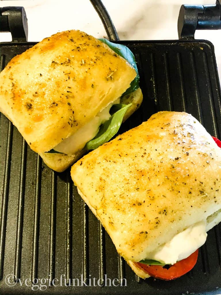 two caprese paninis on panini grill ready to be cooked