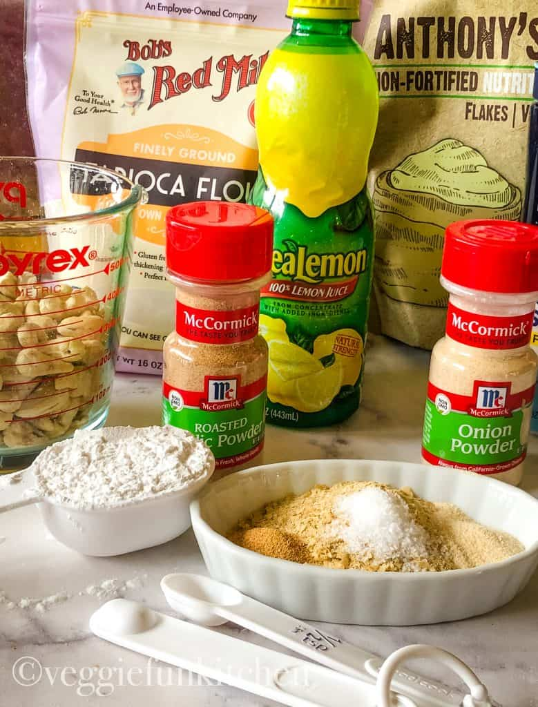 Ingredients for mozzarella cheese sauce including raw cashews, nutritional yeast, tapioca flour, garlic and onion powders and lemon juice.