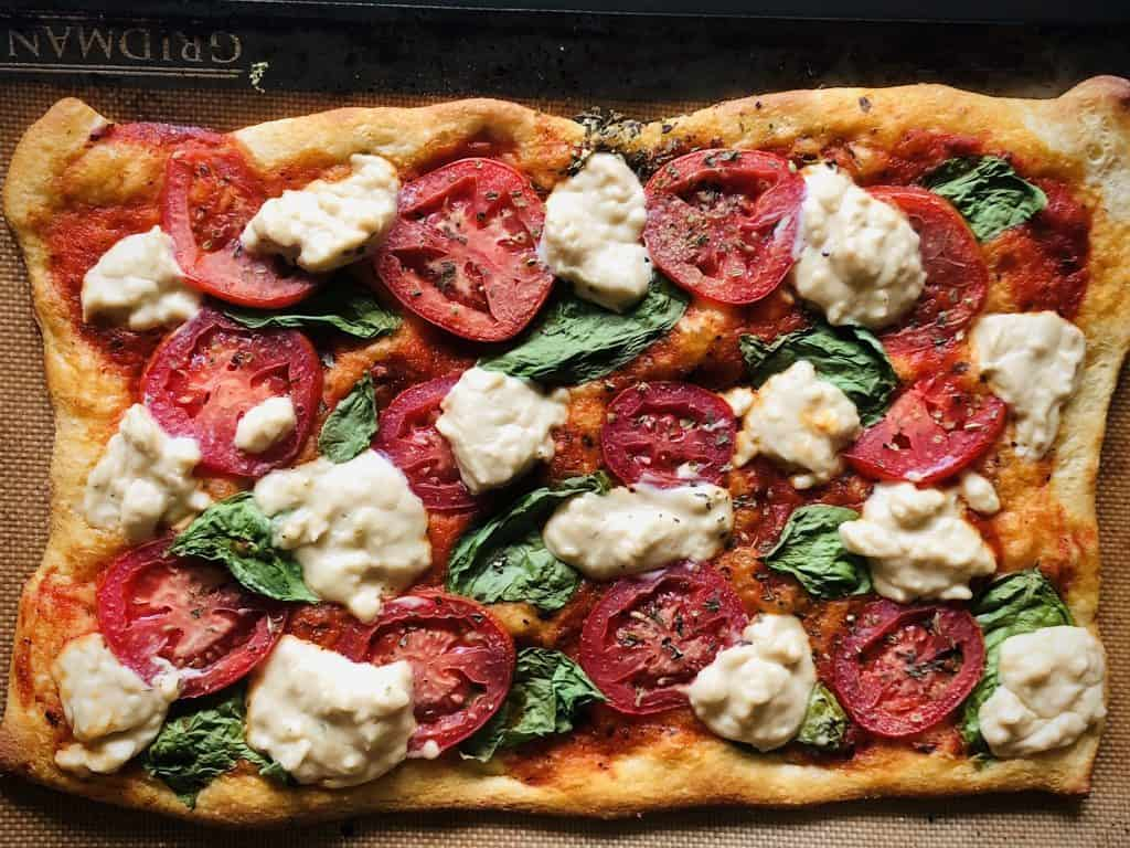 caprese pizza with vegan mozzarella, fresh tomatoes, and basil