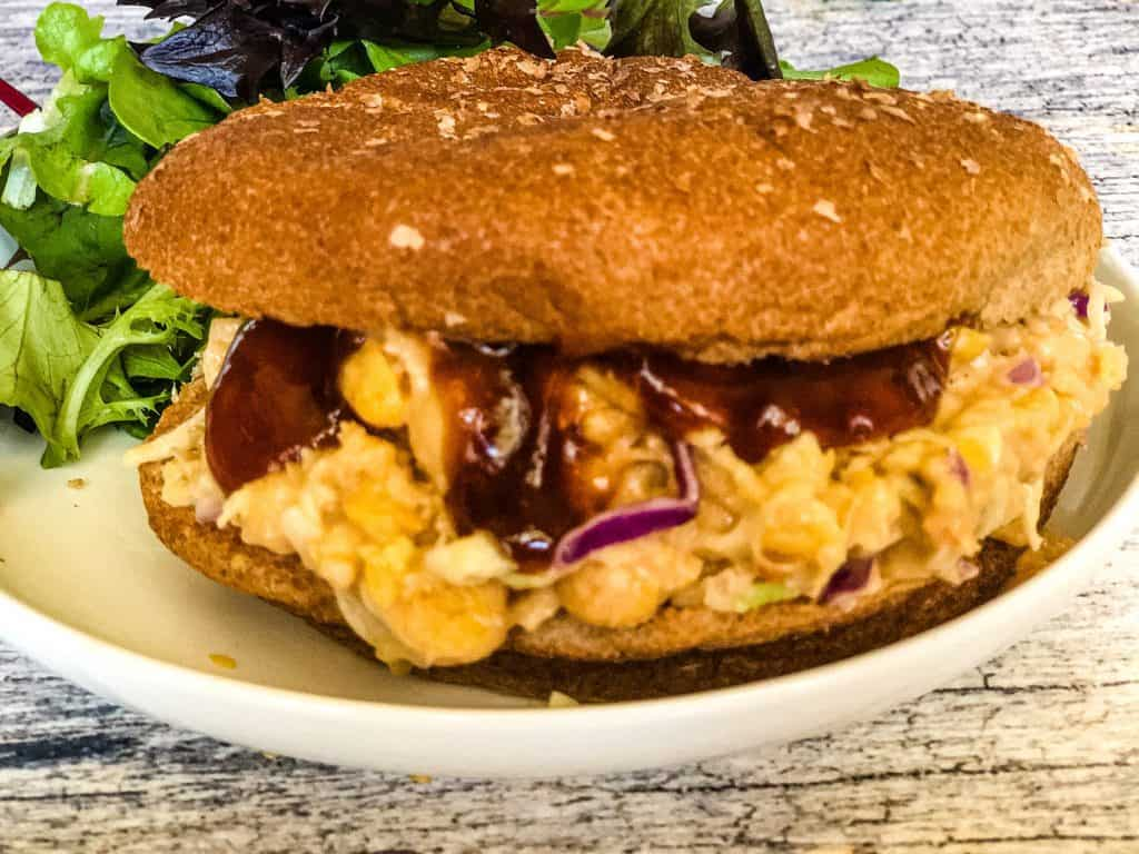 bbq chickpea salad sandwich on whole wheat bun with bbq sauce dipping out with salad