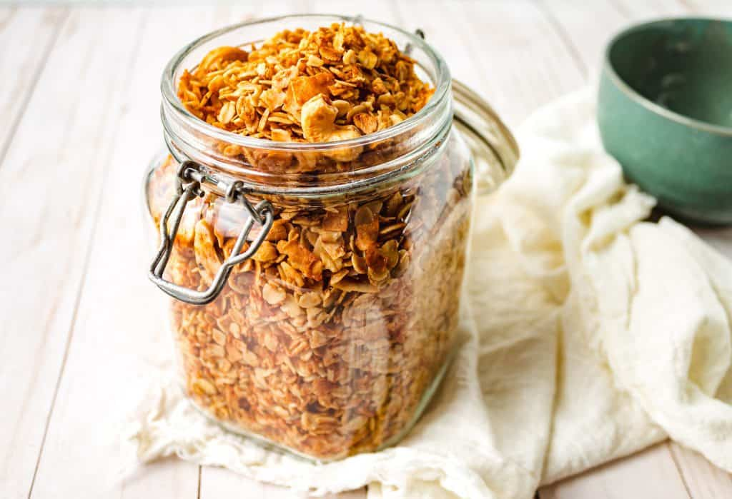 granola in glass jar with white napkin and green bowl