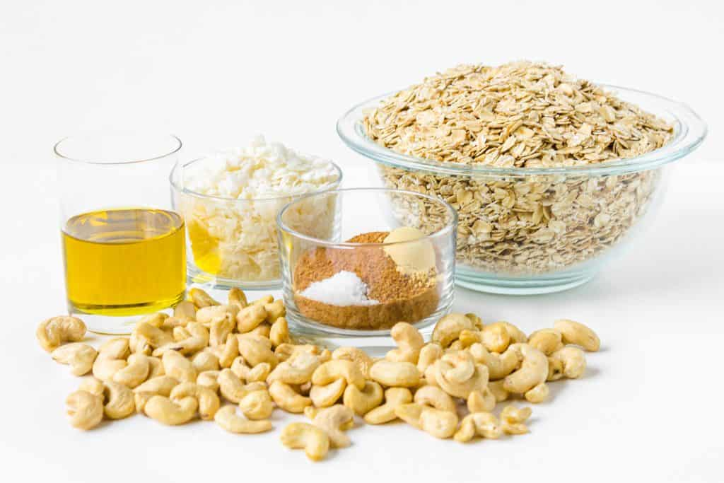 ingredients for granola including oil, coconut, oats, brown sugar, ginger, salt, and cashews
