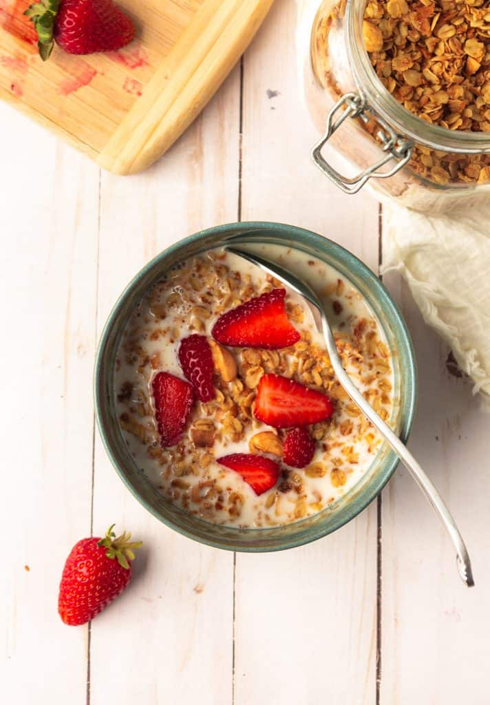 granola in green bowl with almond milk and strawberries