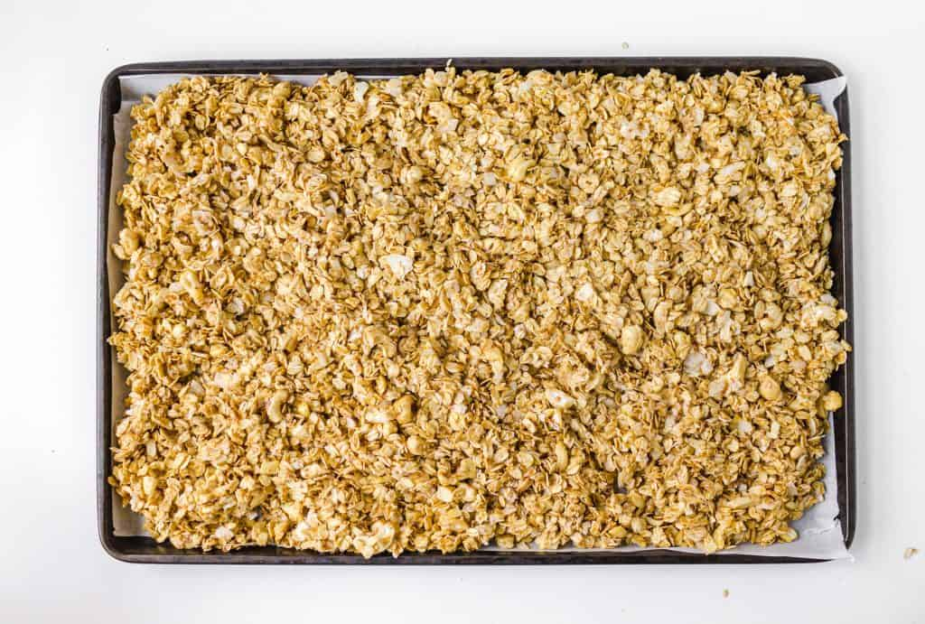 uncooked granola spread on pan with parchment