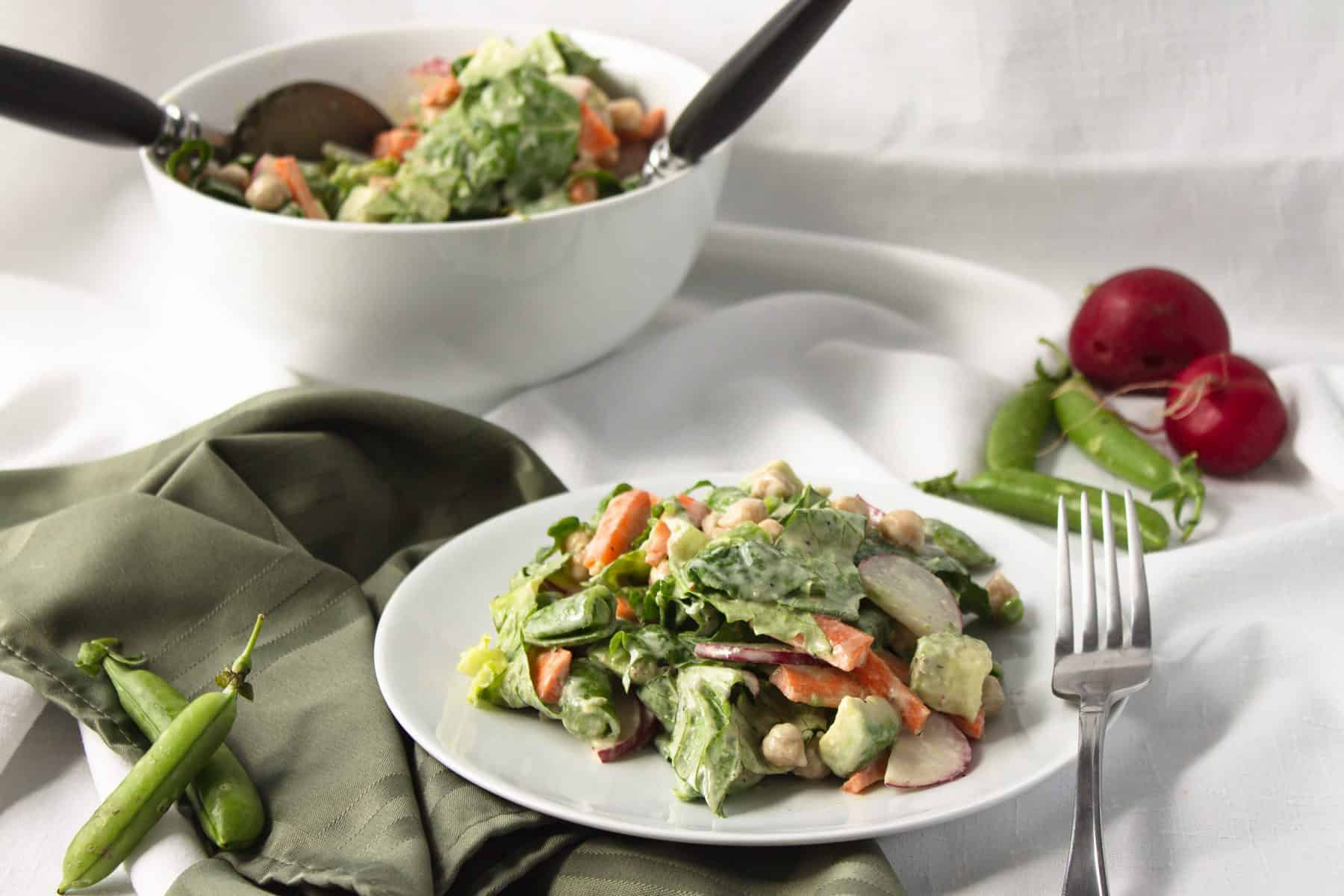 veggie salad in white bowl with fork and spoon in bowl and salad on white plate with green napkin and fork. Radishes and snap peas in backgroun