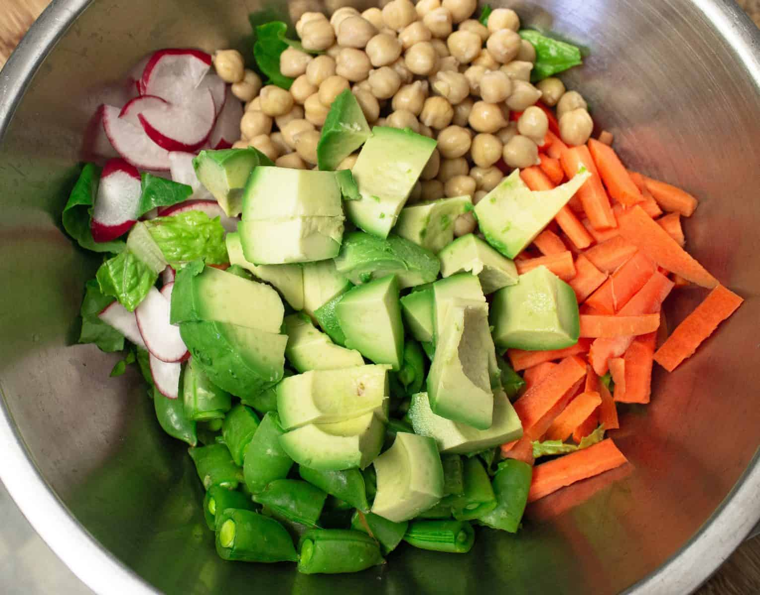 fresh veggies in metal bowl for salad. Vegetables include romaine lettuce, sliced radishes, chickpeas, chopped carrots, and chopped avocado