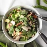 veggie salad in white bowl with green napkin and fork and spoon in bowl