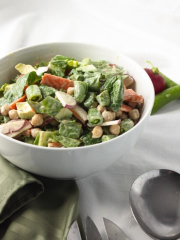 veggie salad in white bowl with green napkin and fork and spoon