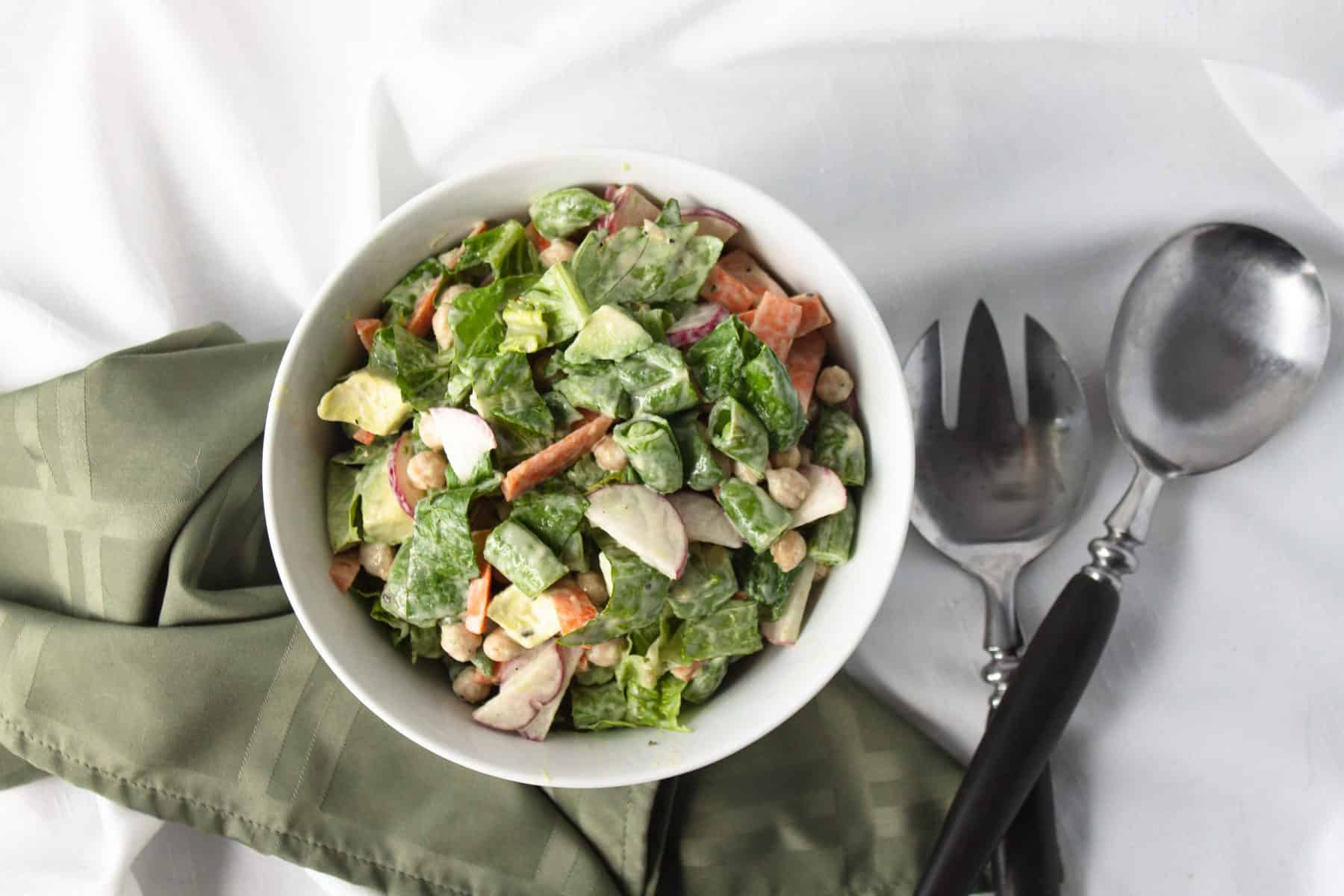 overhead view of veggie salad in white bowl with green napkin and fork and spoon