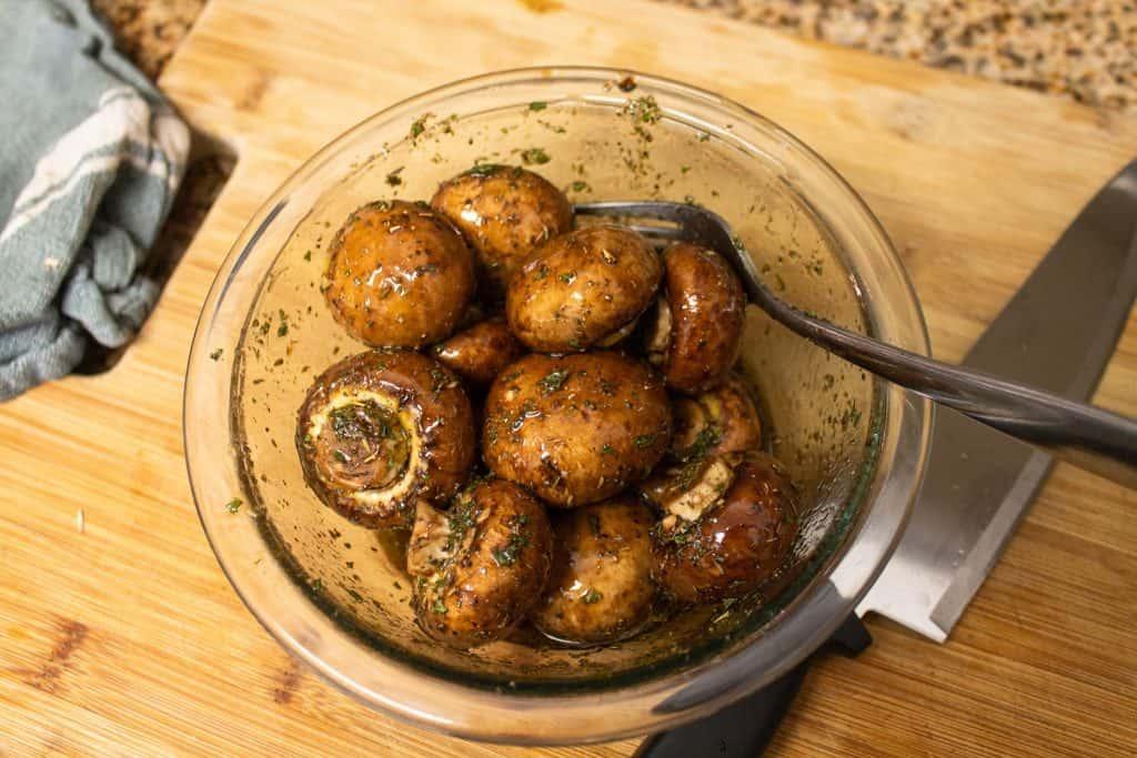 mushrooms marinating in glass bowl