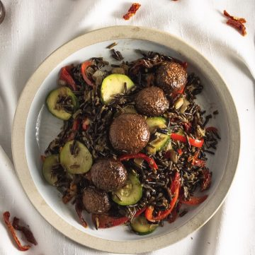 Tan bowl of marinated mushrooms on a bed of wild rice and vegetables. on a white cloth with bits of sun-dried tomatoes scattered about