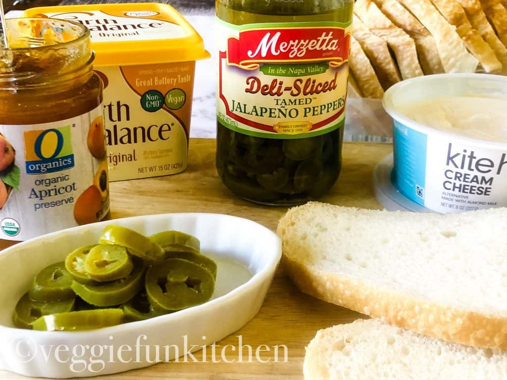 Ingredients for cream cheese panini including apricot preserves, vegan butter spread, jalapeños, vegan cream cheese, bread