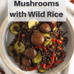 Marinated mushrooms and wild rice with veggies in a tan bowl with pinterest text overlay
