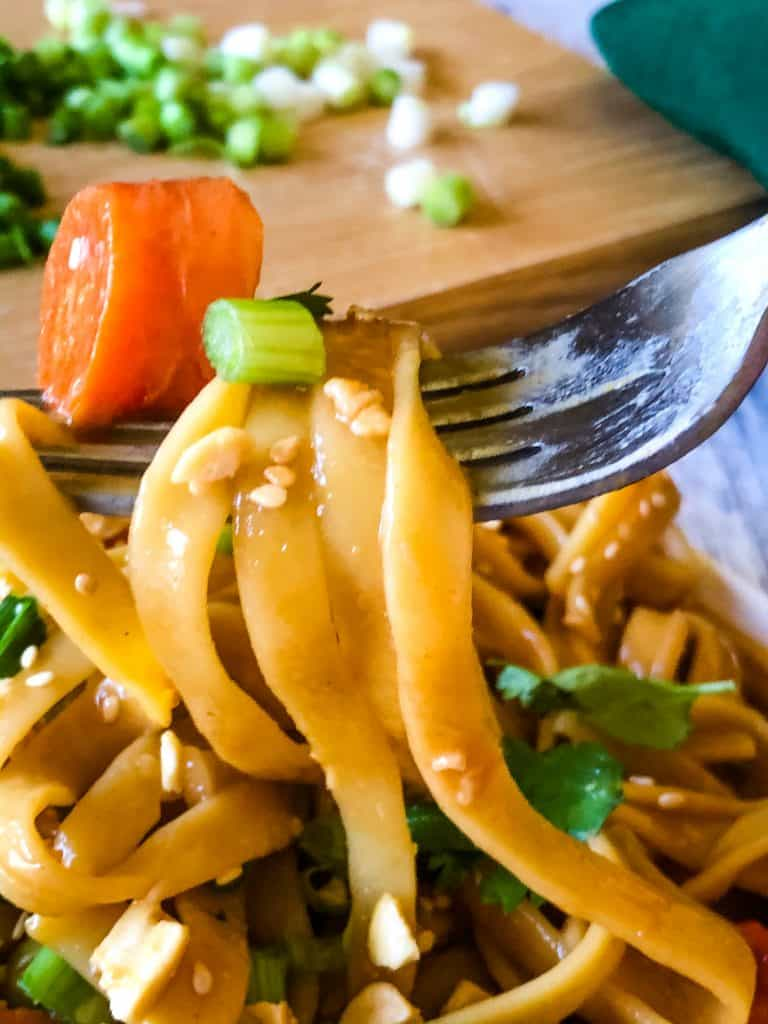 fork of peanut butter noodles with chopped green onions on wooden cutting board in background