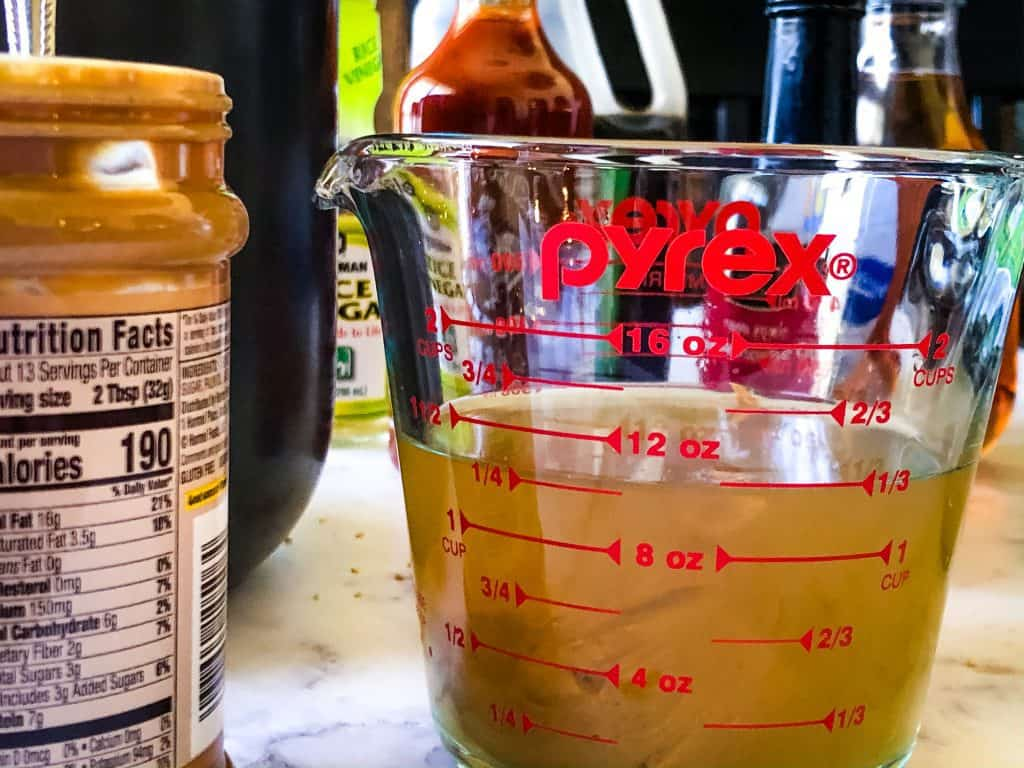 close up of measuring cup with vegetable broth and peanut butter