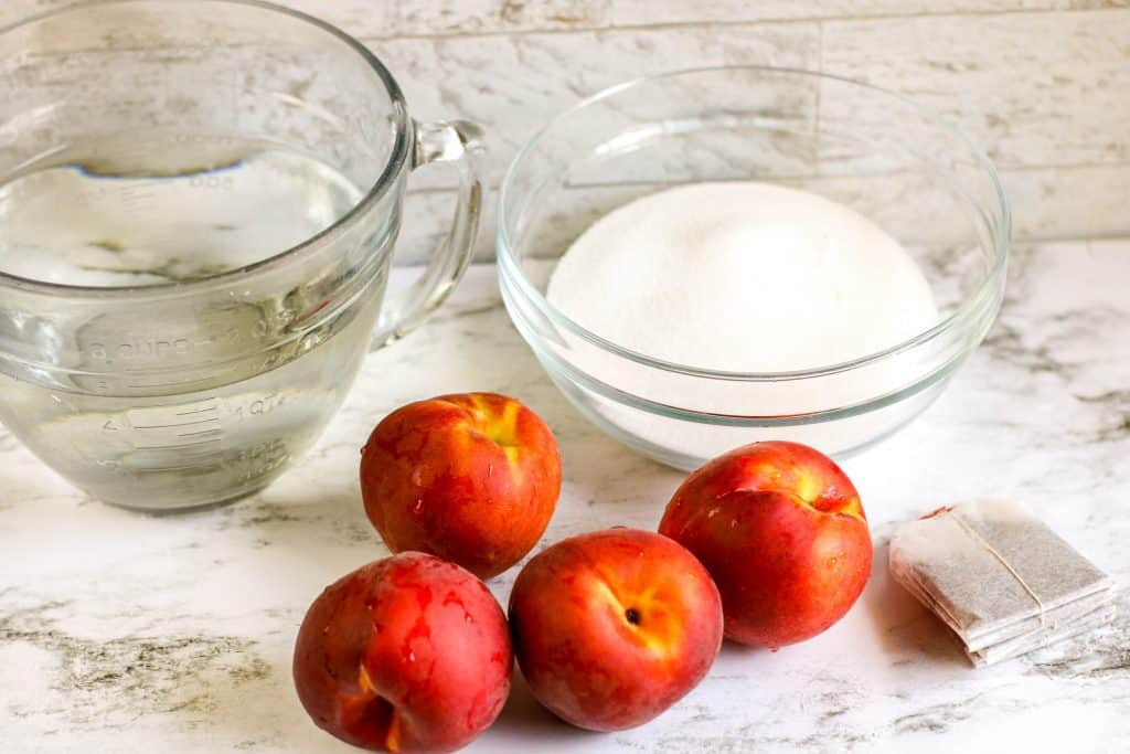 ingredients needed for peach iced tea including water, peaches, sugar, and tea bags