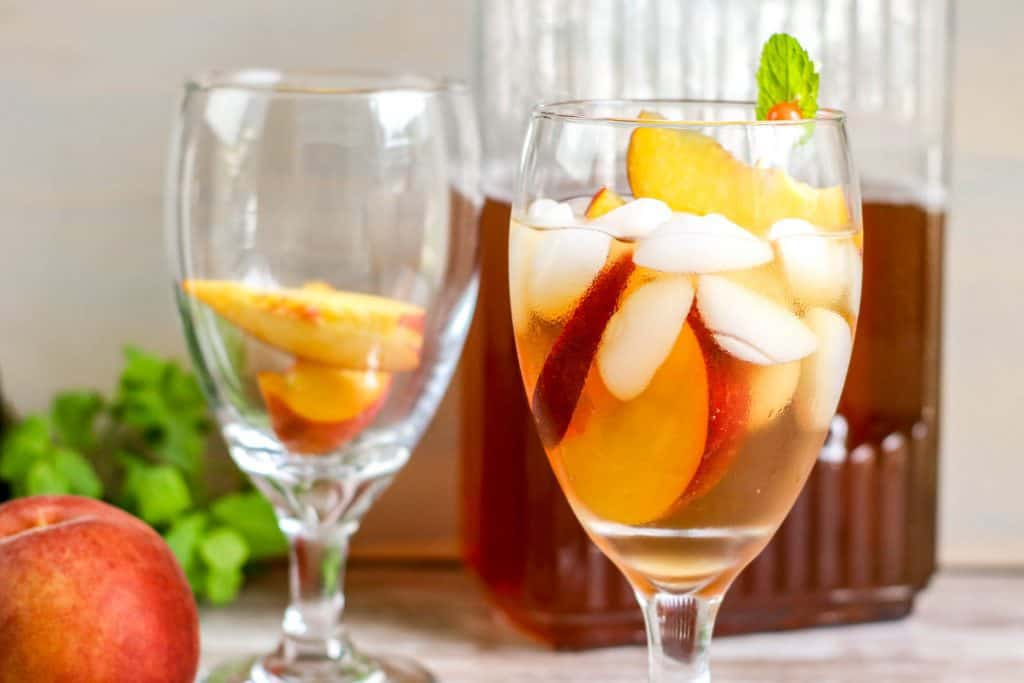 two stemmed glasses - one filled with peaches, the other with peaches and iced tea with peach in foreground and glass picture of tea in background
